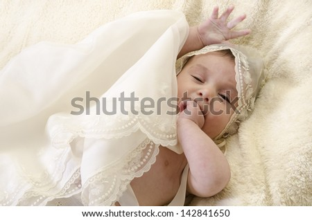 Baby with ceremonial clothes biting her hand - stock photo