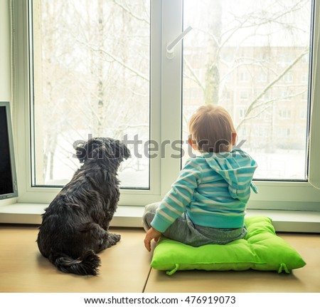 Baby with Dog Looking through a Window in Winter. Boy and Pet Friends Concept. Rear View with Backlit. Toned Photo with Copy Space.