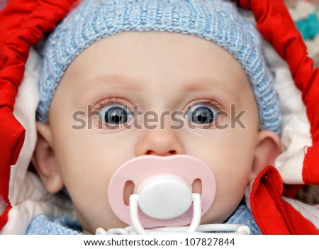 baby with dummy making a funny surprised face - stock photo