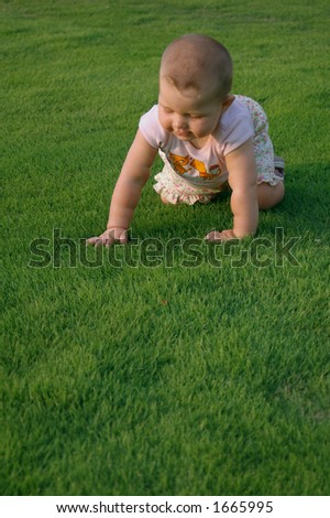 baby with funny face on grass - stock photo