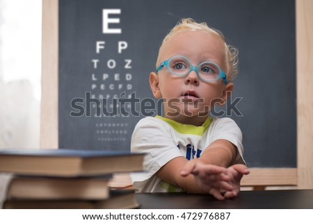Baby with glasses sits at a table on the background of the table for an eye examination