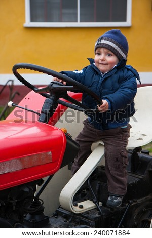 baby with hat driving a tractor old - stock photo