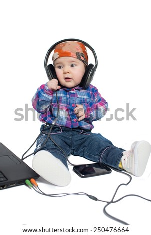 baby with headphones sitting on a white background.