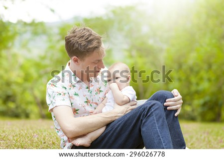 Baby with his father sitting on green grass outdoors in spring park. family outside - stock photo