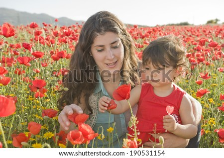 baby with his mother enjoying a field day outdoors - stock photo