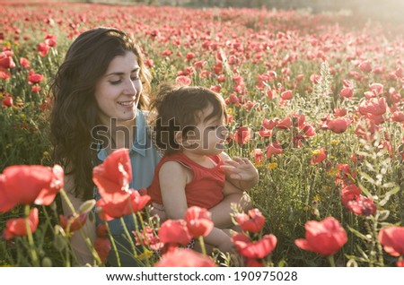 baby with his mother enjoying a field day outdoors, smiling in sunset back light - stock photo