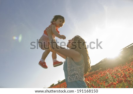 baby with his mother enjoying a field day outdoors, smiling in sunset backlight flare - stock photo