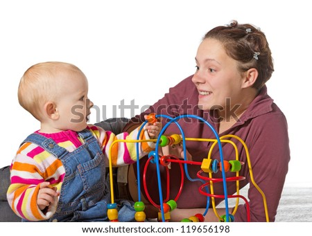 Baby with motor activity development delay being stimulated to develop coordination and muscle control and movement on a bead maze by an adoring mother - stock photo