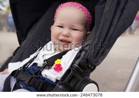 Baby with new teeth in stroller - stock photo