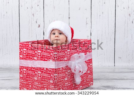 baby with red cap sitting in xmas giftbox - stock photo