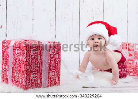 baby with red cap with ribbon and gift