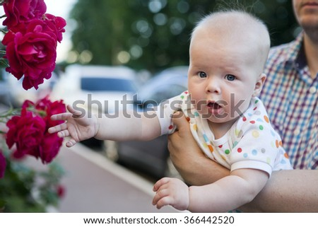 Baby with rose flower in garden - stock photo