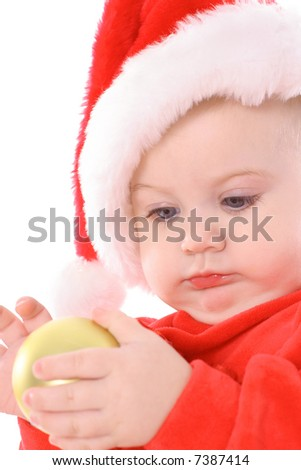 baby with santa hat holding ornament - stock photo