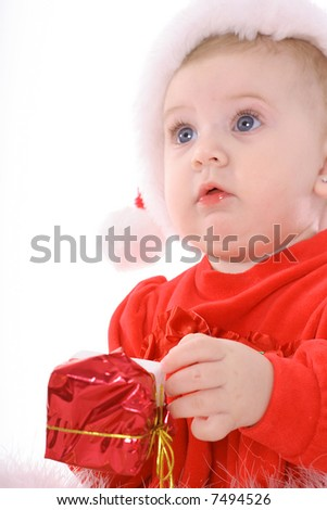 baby with santa hat holding present - stock photo