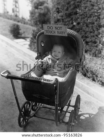 Baby with sign saying do not touch baby - stock photo