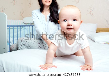 Baby with smile hanging out on a bed in a room with  mother. The child smiles, Mom laughs.