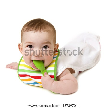 Baby with spoon in mouth looking at camera - stock photo