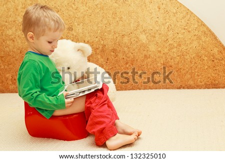baby with touch pad sitting on the pot - stock photo