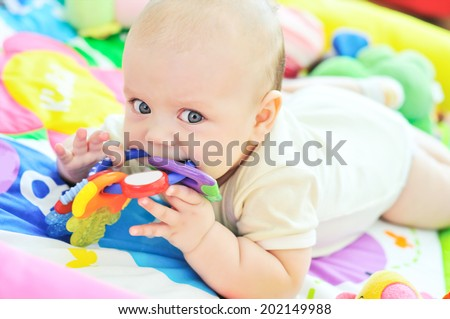 baby with toy on the carpet - stock photo