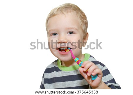 Baby with white first teeth brushing teeth with a toothbrush. White little boy with a toothbrush in his hand. Baby chewing on children's toothbrush prevention of dental diseases.On a white background