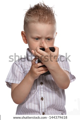 Baby, young boy watching concentrated a smart phone on a white isolated background, junior plays with mobile smartphone - stock photo
