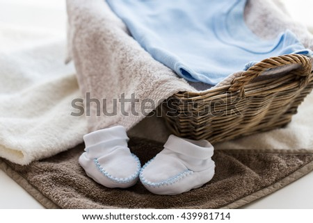 babyhood, motherhood and object concept - close up of white baby bootees with pile of clothes and towel for newborn boy in basket on table - stock photo