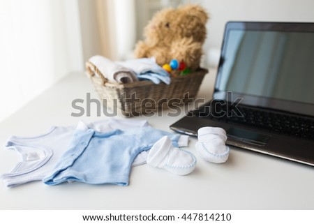 babyhood, motherhood, clothing, technology and object concept - close up of baby clothes and toys for newborn boy in basket with laptop computer at home - stock photo