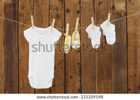 Babywear and booties against wooden background - stock photo