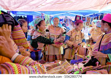 BAC HA, VIETNAM - NOV 21: Unidentified women of the Flower H'mong Ethnic Minority People at market on November 21, 2010 in Bac Ha, Vietnam. H'mong are the 8th largest ethnic group in Vietnam - stock photo
