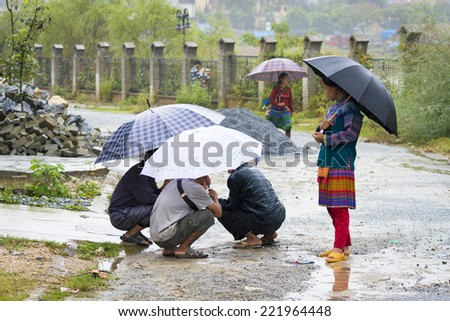 BAC HA, VIETNAM - SEP 21, 2014: Unidentified people  under umbrellas at the Bac Ha Market, a large Sunday market with people wearing beautiful colored minorities�¢?? costumes