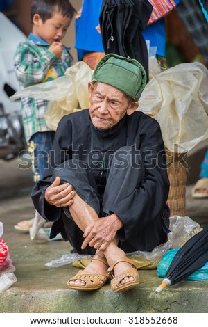BAC HA, VIETNAM - SEP 21, 2014: Unidentified Vietnamese old man at the Bac Ha Market, a large Sunday market with people wearing beautiful colored minorities costumes