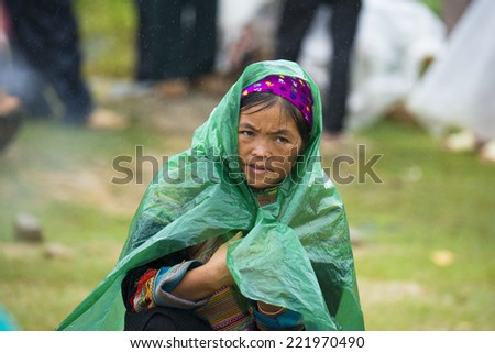 BAC HA, VIETNAM - SEP 21, 2014: Unidentified Vietnamese woman covered of the rain at the Bac Ha Market, a large Sunday market with people wearing beautiful colored minorities�¢?? costumes