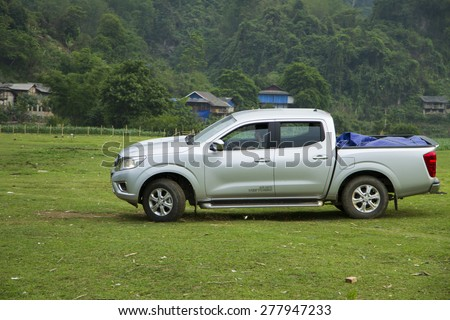 Bac Kan, Viet Nam - Apr 24, 2015: Nissan NP300 Navara car crossing glass fields in Babe lake in Vietnam