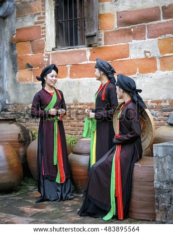 BAC Ninh, Vietnam, August 21, 2016 group of young women, Bac Ninh province, Vietnam. wearing traditional costumes. standing next to old temple