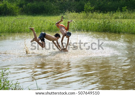Bac Ninh, Vietnam - May 29, 2016: Children catching fish by fishing bamboo trap - the old traditional way, on pond in Bac Ninh province