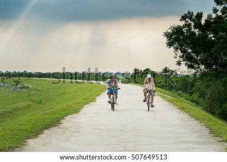 Bac Ninh, Vietnam - May 29, 2016: Two men cycling on dyke by Cau river in Bac Ninh province