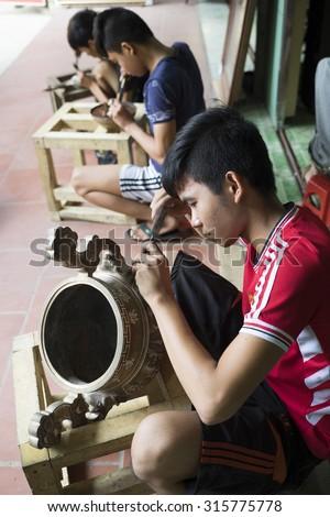 Bac Ninh, Vietnam - Sep 12, 2015: Junior craftsmen making copper handicraft products in traditional way (hand work) in Dai Bai village. Junior people are major labors in traditional works in Vietnam. - stock photo