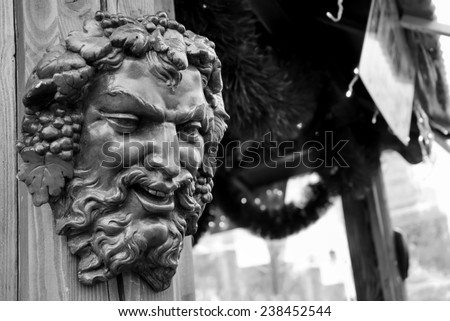 Bacchus (Dionysus) mask attached to the mulled wine stall at Christmas market in Paris (France). Aged photo. Black and white. - stock photo