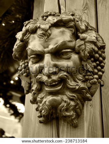 Bacchus (Dionysus) mask attached to the mulled wine stall at Christmas market in Paris (France). Aged photo. Sepia. - stock photo
