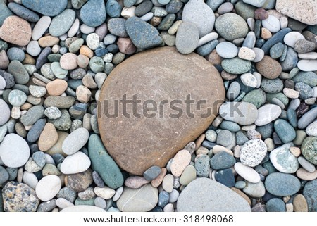 Bacground made of pebbles on the beach with one big pebble in the centre - stock photo