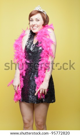 Bachelorette in tiara and feather boa with goofy toothy grin - stock photo