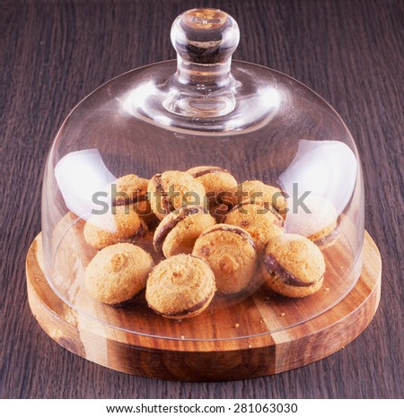 Baci di dama biscuits under glass jar bell, wooden background, horizontal image - stock photo