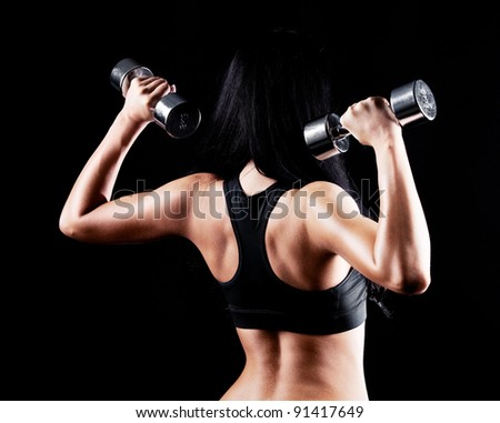 back and hands of a young brunette sporty muscular woman working out with two metal dumbbells, isolated against black background