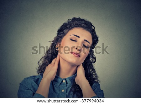 Back and spine disease. Closeup portrait tired woman massaging her painful neck isolated on gray wall background. Human face expression. Chronic fatigue disease - stock photo