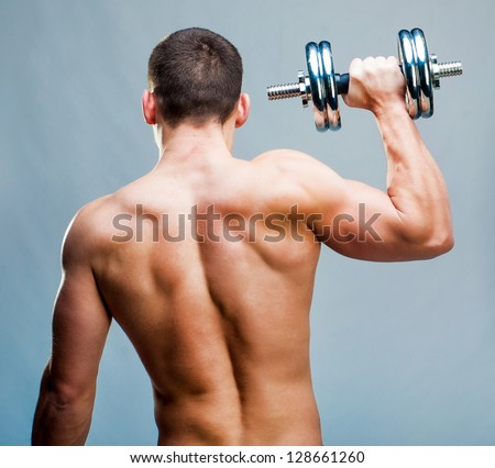 back attractive athletic man with dumbbells - stock photo