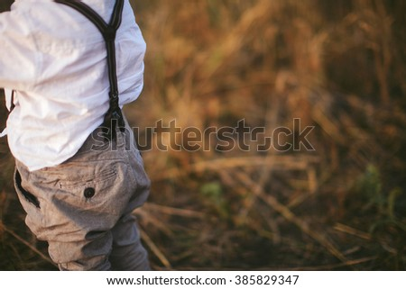 back boy in a shirt with suspenders standing in a field