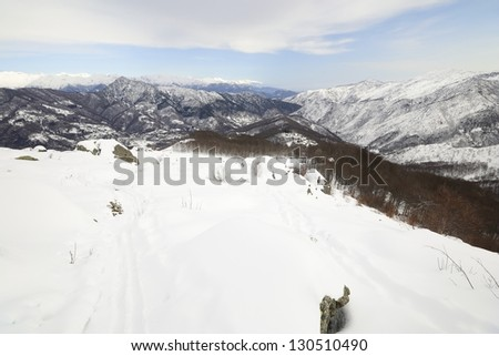 Back country ski tracks in scenic winter mountainscape and cloudscape in backlight effect - stock photo