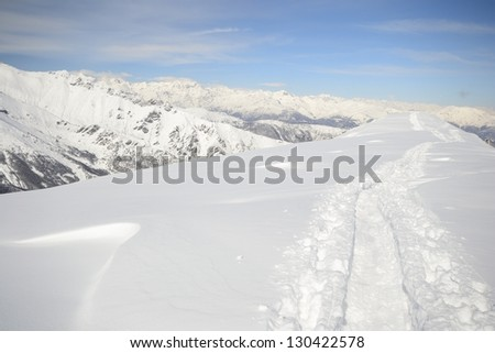 Back country ski tracks in scenic winter mountainscape with candid slope covered by thick powder snow - stock photo