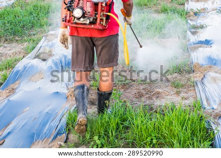 Back farmer spraying pesticides fertilizers grass  for farm agriculture - stock photo