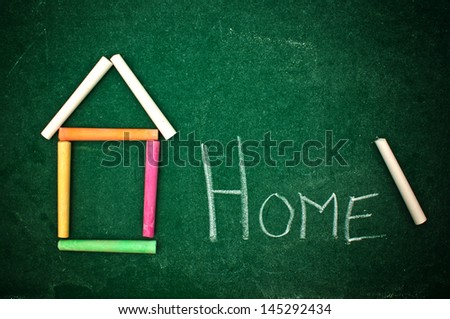 Back home, handwritten letters on a green chalkboard. Colorful chalks forming the shape of a house or a school building. - stock photo